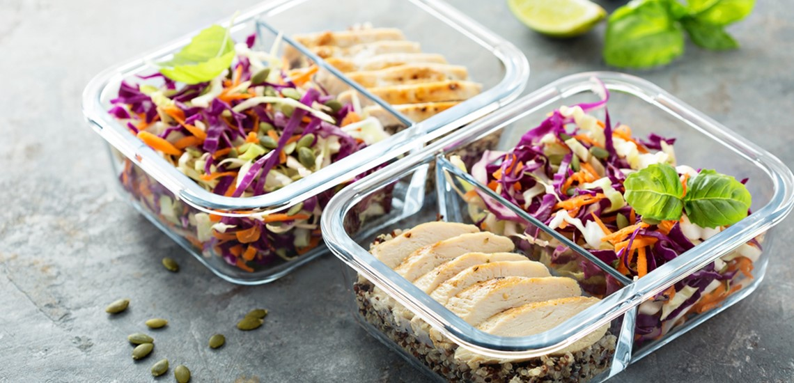 Chicken, rice and quinoa with salad meal prep in glass food containers